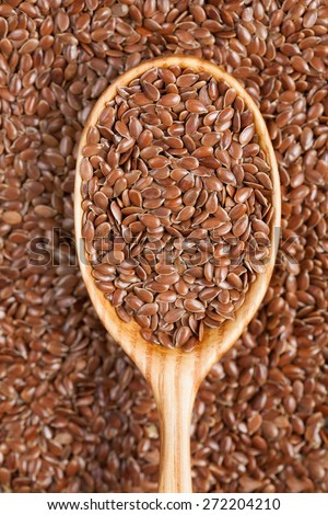 Healthy raw brown flax seeds in vintage wooden spoon - stock photo