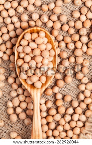 Healthy raw chickpeas nutrition super food in wooden spoon on vintage textile background - stock photo