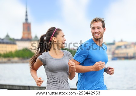 Healthy runners running in Stockholm city cityscape background. Riddarholmskyrkan church in the background, Sweden, Europe. Healthy multiracial young adults, asian woman, caucasian man.