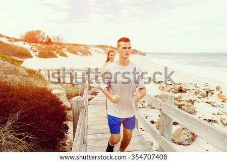 Healthy running man on beach - stock photo
