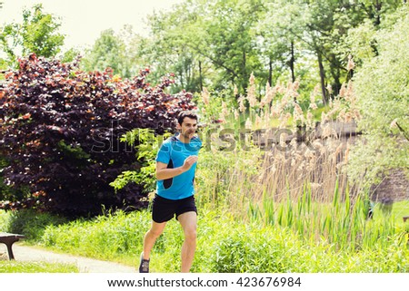 Healthy running runner man workout in a city park. Jogging male fitness model working out training  on park road. - stock photo