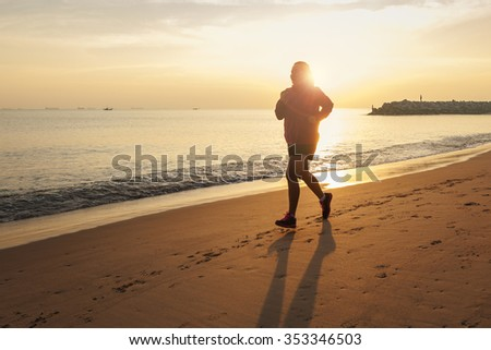 Healthy running runner woman during sunset on the beach workout jog. sunflare through the mist gives atmospheric feel and depth to these fitness images
