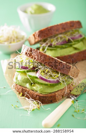 healthy rye sandwich with avocado cucumber alfalfa sprouts - stock photo