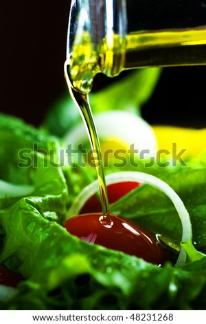 Healthy Salad and pouring olive oil closeup - stock photo