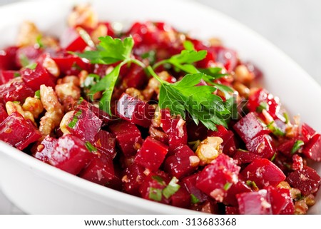 Healthy salad from beet root, walnut and cilantro. Close up, tilted view.
