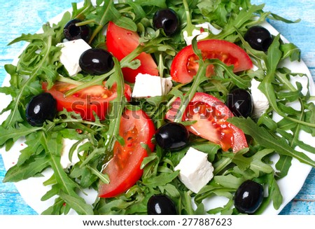 healthy salad of arugula, cheese, tomato and olives