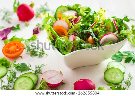 Healthy salad with fresh vegetables and ingredients on white background - stock photo