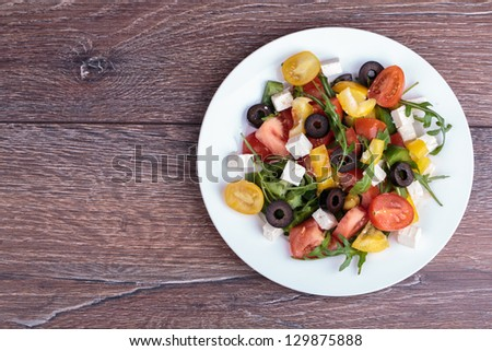 Healthy salad with fresh vegetables on wooden background - stock photo