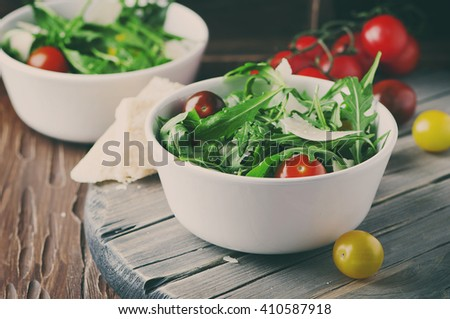 Healthy salad with rocket, tomato and parmesan cheese, selective focus and toned image