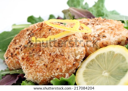 Healthy salmon cakes on bed of lettuce with lemon garnish - stock photo
