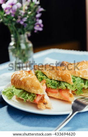Healthy sandwich cut into pieces to show tasty ingredients salami, tomatoes, lettuce. - stock photo