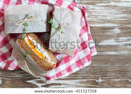 Healthy sandwich made of a fresh rye roll with tasty ingredients of ham, tomato, lettuce and arugula, presented on old wooden board, copy space, top view - stock photo