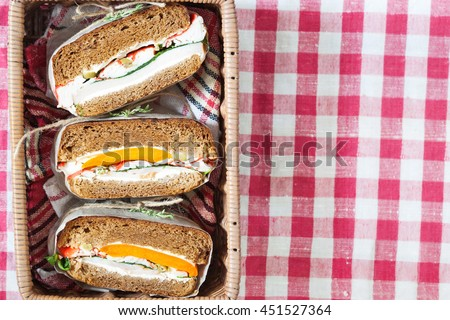 Healthy sandwich made of a fresh rye roll with tasty ingredients of ham, tomato, lettuce and arugula, presented in the basket, top view, copy space - stock photo