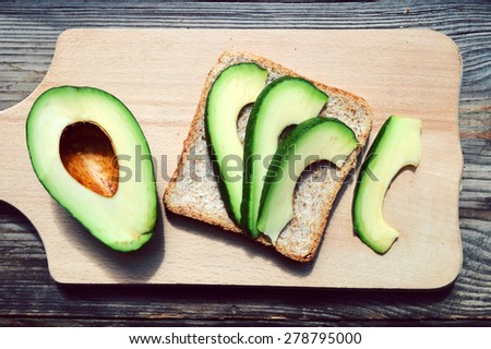 Healthy sandwich with green avocado on wooden table - stock photo