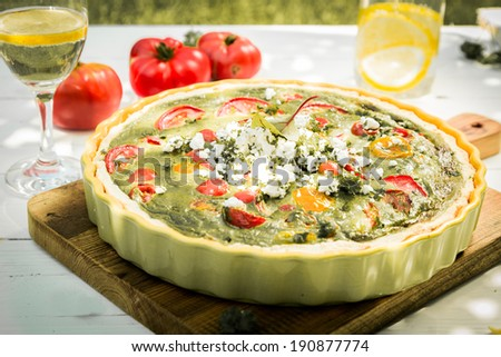 Healthy savory vegetarian quiche with egg custard, herbs, cheese and tomato served for lunch with a glass of chilled white wine, tomatoes and olive oil in the background - stock photo
