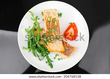 healthy sea food : roasted pink salmon fillet garnished with rocula, and tomatoes on white dish isolated over black background - stock photo