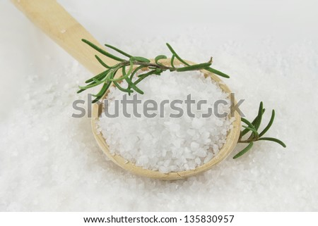 Healthy sea salt on wooden spoon closeup, and rosemary