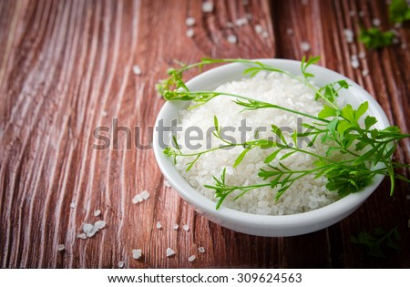 Healthy sea salt with herbs on wooden background