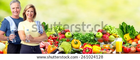 Healthy senior couple over fresh fruits and vegetables background. - stock photo