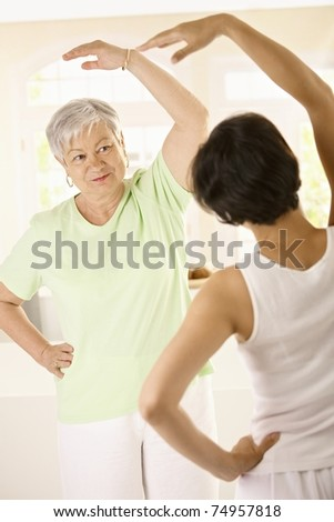 Healthy senior woman doing exercises with personal trainer at home, smiling.? - stock photo