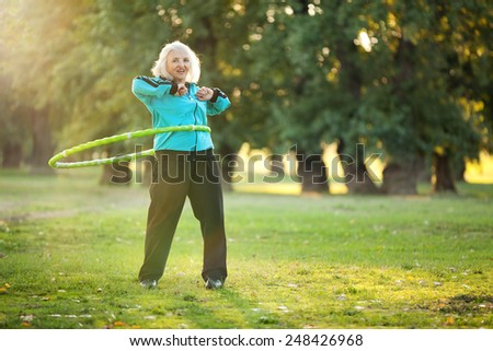 Healthy Senior Woman doing Exercises with the Plastic Hoop at the Green Meadow in the Bright Autumn Evening - stock photo