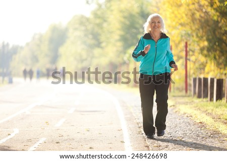 Healthy Senior  Woman Jogging at the Pedestrian Walkway in the Bright Autumn Evening - stock photo