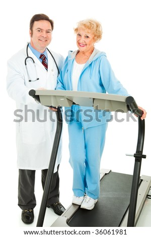 Healthy senior woman on a treadmill, standing beside her doctor.  Isolated on white.