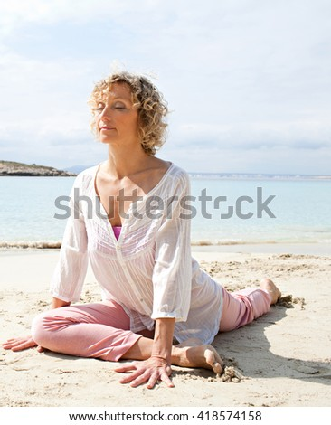 Healthy senior woman stretching in yoga position, meditating on the shore of transparent sea in a coastal beach destination with eyes closed, sunny outdoors. Sporty travel lifestyle, nature exterior. - stock photo