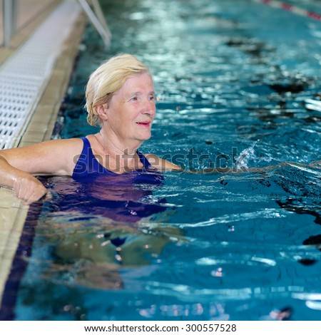 Healthy senior woman swimming in the pool. Happy pensioner enjoying sportive lifestyle. Active retirement concept. - stock photo