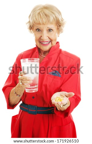Healthy senior woman taking omega 3 fish oil supplements with a glass of ice water.  Isolated on white.   - stock photo