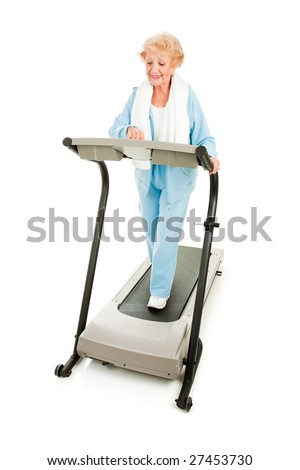 Healthy senior woman walking on a treadmill.  Full body isolated on white.