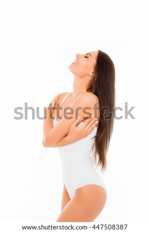 Healthy slim happy brunette in white lingerie embracing herself