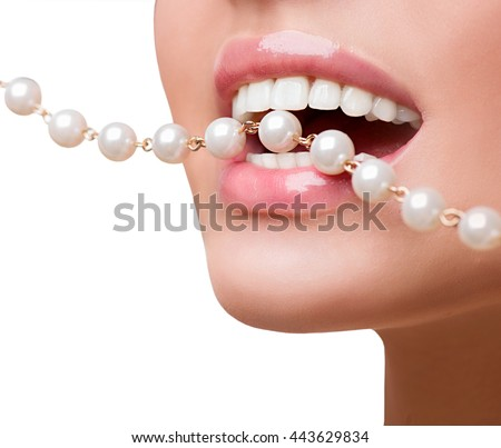 Healthy smile concept. Woman smiles showing white teeth, holding a pearly necklace in to the mouth, teeth care concept. Beautiful natural full lips and white teeth