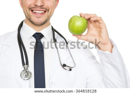 Healthy smile. Cropped closeup shot of a male doctor smiling happily holding an apple isolated on white  - stock photo