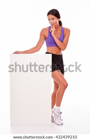 Healthy smiling brunette woman holding blank placard and looking at camera with one hand to her chin while wearing violet and black gymnastic clothing, isolated - stock photo