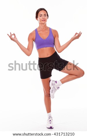 Healthy smiling brunette woman, standing on one leg in a yoga pose, with her eyes closed, smiling while wearing violet and black gymnastic clothing, isolated - stock photo