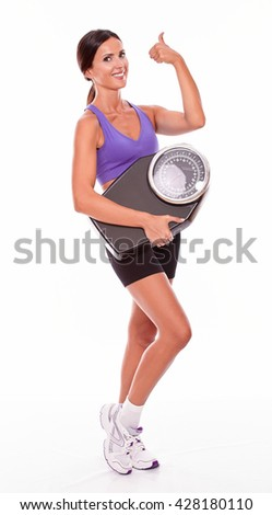 Healthy smiling brunette woman with a scale, gesturing a thumb up sign while wearing her hair tied back and violet and black gymnastic clothing, isolated - stock photo