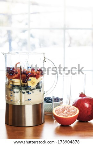 Healthy smoothie ingredients in blender with fresh fruit ready to blend on kitchen table