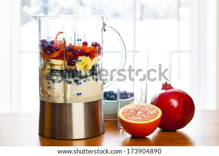 Healthy smoothie ingredients in blender with fresh fruit ready to blend on kitchen table - stock photo