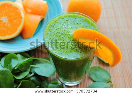 Healthy smoothie with spinach and orange in a glass - stock photo