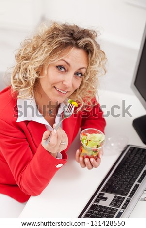 Healthy snack at the office - woman eating fresh vegetables mix - stock photo