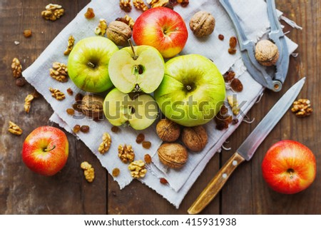 Healthy snack background - fruits and nuts. Green and red apples, raisins and walnuts on rustic wooden background. - stock photo