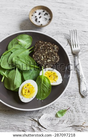 healthy snack - fresh spinach and  egg on a light wooden background - stock photo