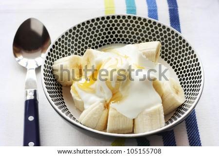 Healthy snack of Banana with yogurt and honey - stock photo