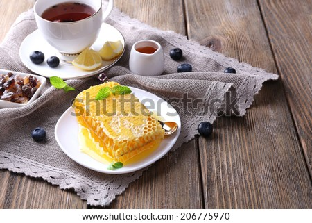 Healthy snack with fresh honey on wooden table