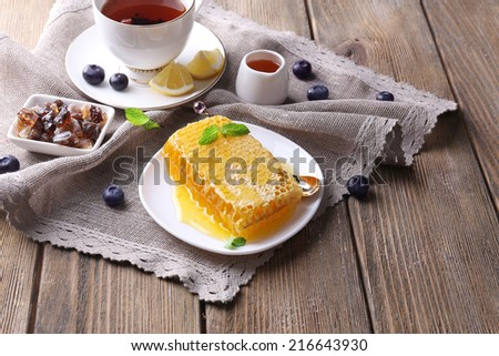 Healthy snack with fresh honey on wooden table - stock photo