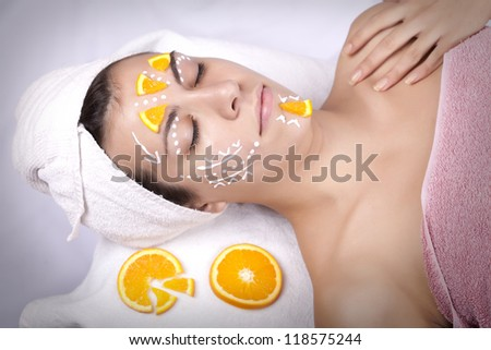 Healthy spa: portrait if a young beautiful woman having moistening mask applied on her face with slices of oeange  and towel on top of her head - stock photo