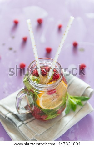 Healthy Spa Water with Fruit. Vitamin water with lemon, mint and raspberries in a jar with straw against a lilac wood background. - stock photo