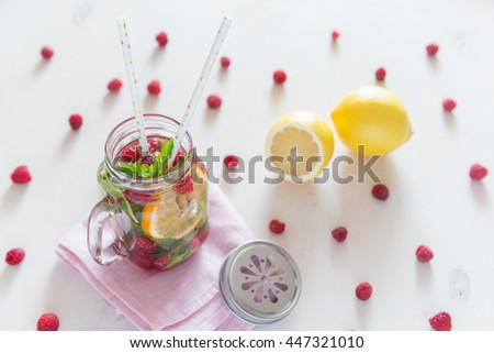 Healthy Spa Water with Fruit. Vitamin water with lemon, mint and raspberries in a jar with straw against a white wood background. Available space at right side. - stock photo