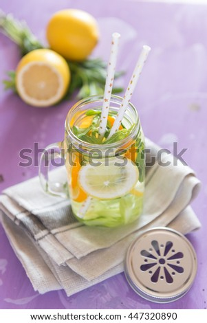 Healthy Spa Water with Fruit. Vitamin water with lemon, mint, celery and cucumber in a jar with straw against a lilac wood background. - stock photo
